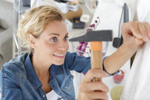 Obraz na plátně a woman hammering a wall