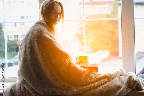 pretty smart thoughtful smiling redhead young girl reading book and drinking cof Canvas Print