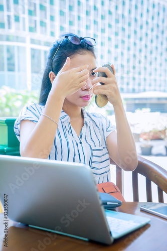 Portrait of young woman touching her face in cafe