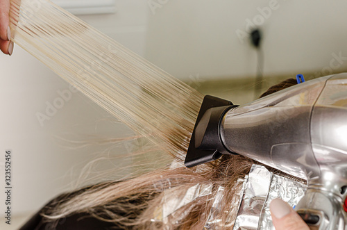 Tela Process of applying blow dryer to blow away short hair for AirTouch technique