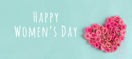 Women's day banner.postcard favorite.Festive wreath of roses decoration with gifts and pink roses on a blue background. copyspace.flat lay