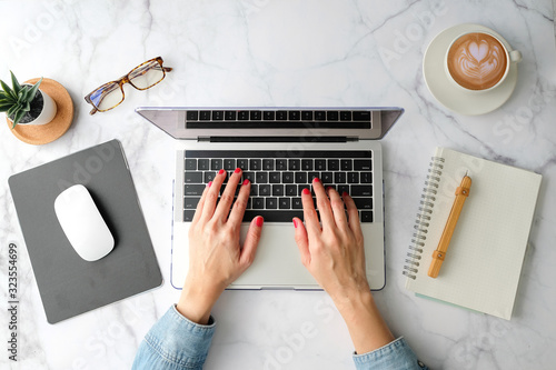 Flat lay workspace. Woman working on laptop coffee cup, smartphone, computer, notebook, planner and stationary with copy space on marble table background.
