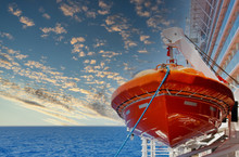 An Orange Lifeboat Hanging Over A Blue Sea On The Side Of A Cruise Ship