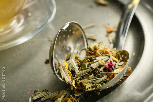 Fototapeta Dry tea leaves and infuser on table, closeup