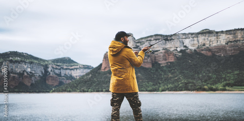 Obraz fishery concept, beard fisherman fishing rod, man enjoy hobby sport on lake, person catch fish on river on background mount, holiday relaxation vacation - fototapety do salonu