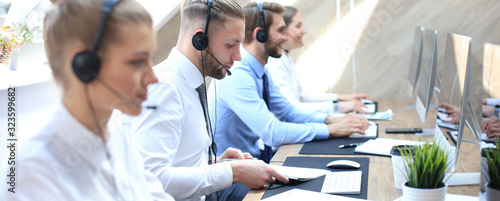 Photo Portrait of call center worker accompanied by his team