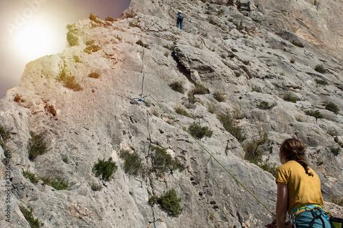 Close-up of rock climber girl belaying a man who climbs on rock. Wallpaper Mural