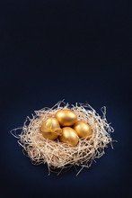 Golden Colored Easter Eggs In Decorative Nest On Dark Blue Background. Happy Easter Greeting Card. Easter Background. Place For Text.