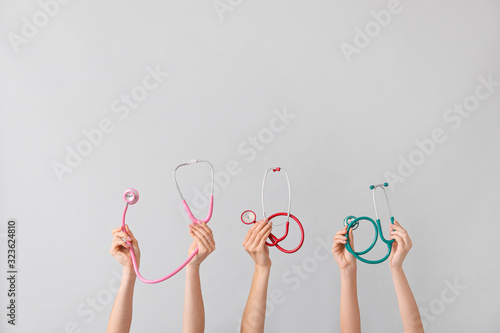 Many hands with stethoscopes on grey background