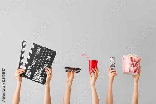 Many hands with popcorn, drink, remote control, movie clapper and eyeglasses on Canvas Print