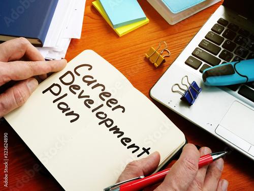 Fototapeta Employee is writing career development plan by pen. obraz