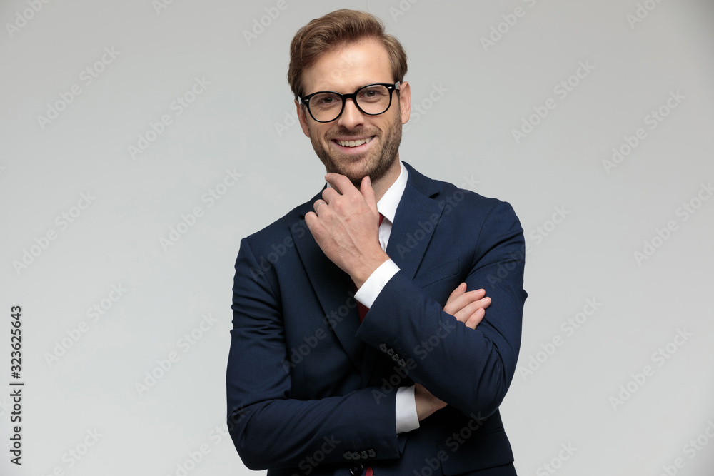 Fototapeta businessman standing with arms folded while touching chin happy