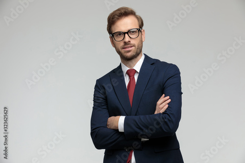 Photo businessman standing with arms crossed and looking ahead satisfied