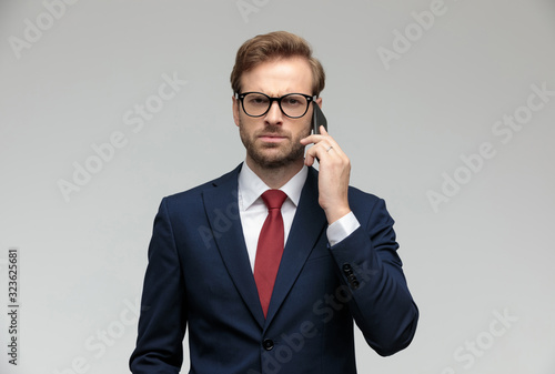 Fototapeta businessman talking on the phone while looking at camera angry obraz