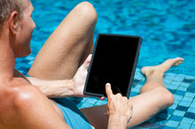Over The Shoulder View Of Man Relaxing With Tablet Computer On The Edge Of Bright Blue Tiled Swimming Pool
