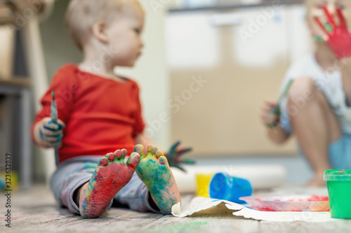 Obraz Adorable cute caucasian little blond siblings children enjoy having fun painting with brush and palm at home indoors . Cheerful happy kids smiling drawing masterpiece art picture. Messy dirty room - fototapety do salonu