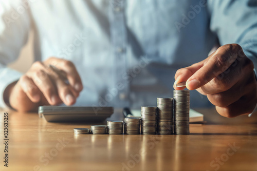 Fototapeta saving money with hand putting coins on stack concept financial obraz