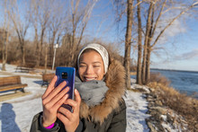 Winter Travel Asian Tourist Woman Taking Selfie Picture With Mobile Phone On Nature Forest Trail Walk Holding Smartphone With Hands Without Gloves, Cold Weather Frostbite Care.