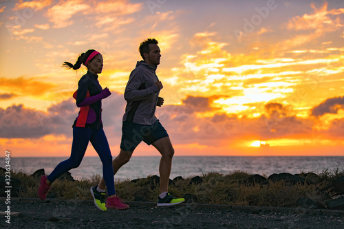 Fototapeta Running people training cardio together active friends jogging in early morning dawn sunrise on beach