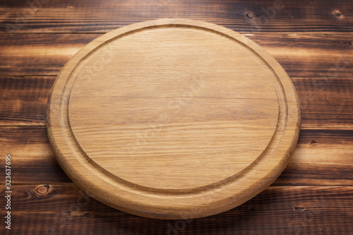 Fotografía pizza cutting board at rustic wooden plank background