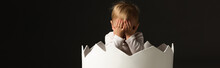 Child Covering Face Inside Eggshell Isolated On Black, Panoramic Shot
