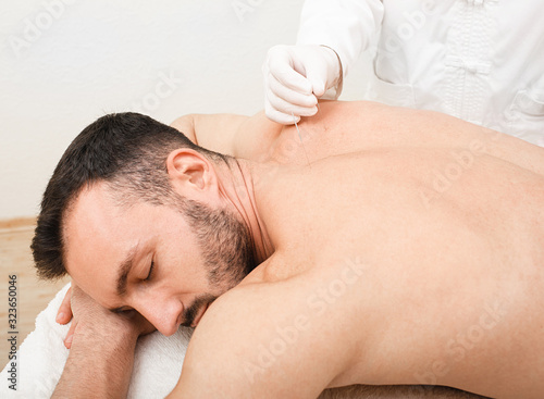 Man enjoys the acupuncture procedure Wallpaper Mural