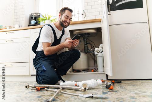 Fotografía Man plumber work in uniform indoors using mobile phone.