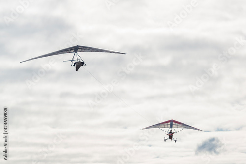 Fotografie, Obraz Motorized hang glider tows another wing.