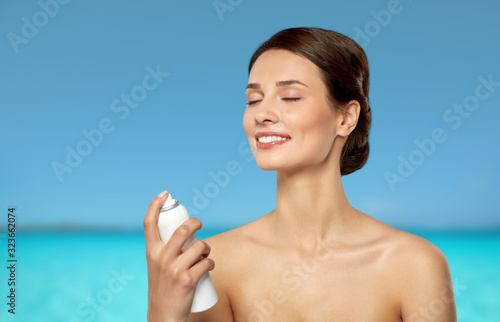 Carta da parati beauty, bodycare and people concept - beautiful young woman applying facial spra