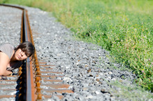Woman Listening For A Incoming Train On The Railroad Track.