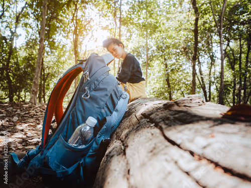 Fototapeta Trekking and camping adventure concept from blue backpack with tired women sitting rest on a log while walk travel nature in forest. obraz
