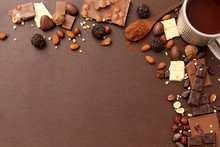 Sweets, Confectionery And Food Concept - Hot Chocolate With Nuts, Candies And Cocoa Powder On Brown Background
