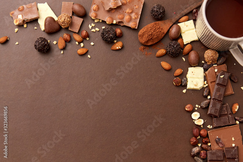 Fototapeta sweets, confectionery and food concept - hot chocolate with nuts, candies and cocoa powder on brown background obraz