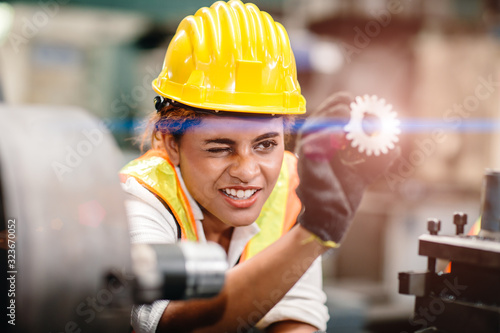Photo engineer worker looking at steel gear part, working precise and most accuracy high performance doing best job
