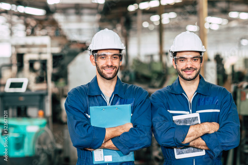 Obraz Portrait of Happy Engineer team smiling worker working together in industry factory. - fototapety do salonu