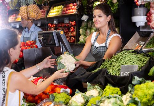 Polite shop assistans selling fruits Canvas Print