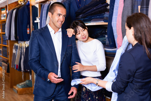 Fototapety, obrazy: Young couple in love looking for mens shirt in clothing store, listening to  recommendations of saleswoman