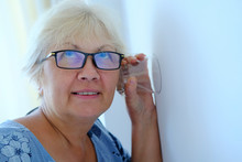 A Woman Uses A Glass Cup To Listen To Neighbors Through The Wall