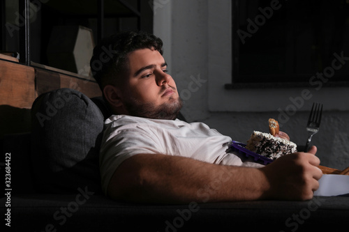 Depressed overweight man eating sweets in living room at night Canvas Print