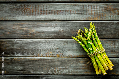 Bunch of asparagus steams on dark wooden background top-down copy space Wallpaper Mural