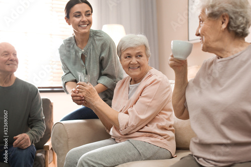 Fotomural Young woman taking care of elderly people in living room