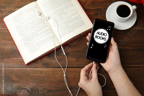 Woman plugging earphones into mobile phone over wooden table with book, top view