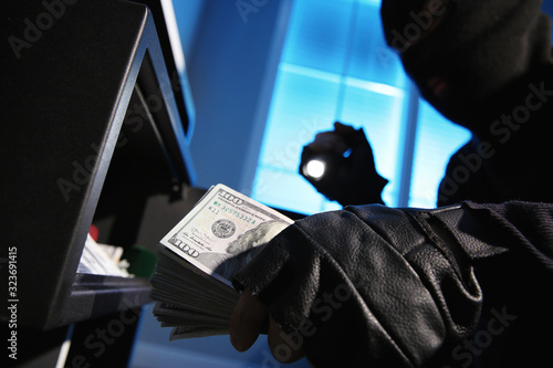 Thief taking money out of steel safe indoors at night, closeup