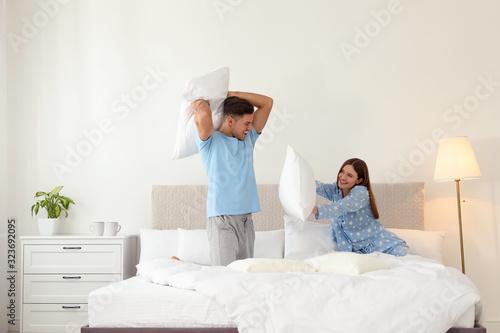 Happy couple having pillow fight in bedroom