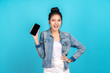 Happy asian woman feeling happiness, blinks eyes and standing hold smartphone on blue background. Cute asia girl smiling wearing casual jeans shirt and connect internet shopping online and present