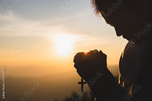 Fotografija Silhouette of young  human hands praying with a  cross at sunrise, Christian Religion concept background
