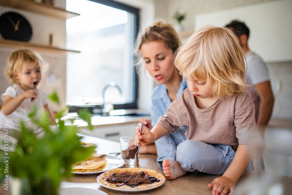 Fototapeta Young family with two small children indoors in kitchen, eating pancakes.