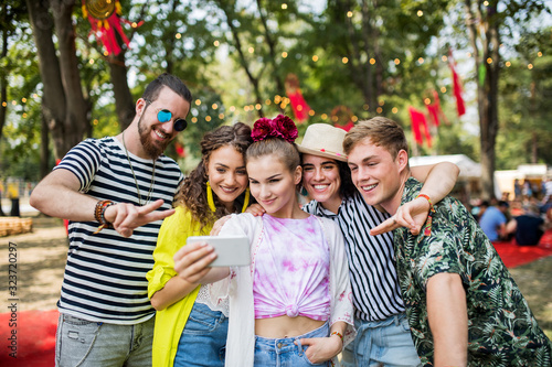 Group of young friends with smartphone at summer festival, taking selfie.