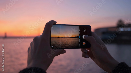 Obraz Close-up of a woman's hands with a phone taking photos of a bright sunset and the sea. - fototapety do salonu