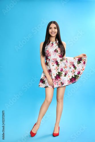 Young woman wearing floral print dress on light blue background